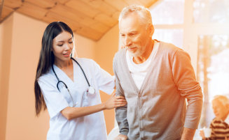 nurse assisting senior man in walking