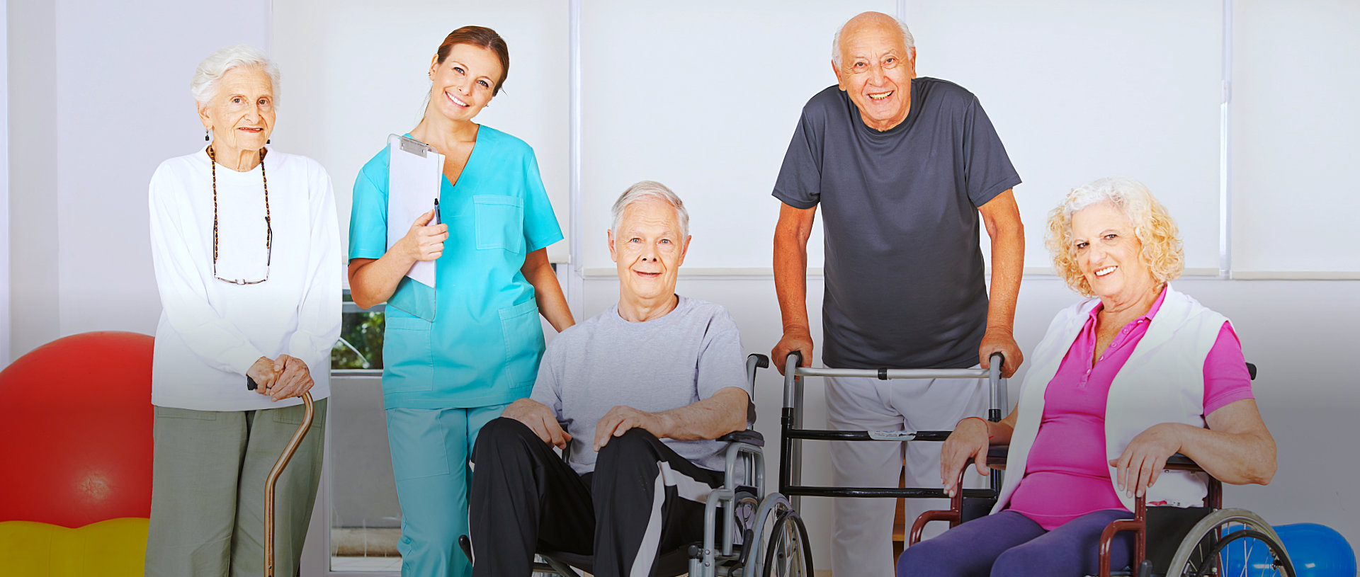 caregiver and group of elderly smiling