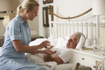 Young nurse handing medecine to an elderly man