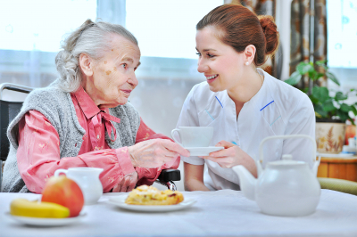 Young nurse handing food to an elderly woman