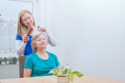 Caregiver combing the elder woman's hair