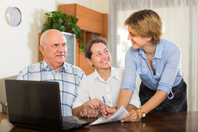 Smiling senior couple answer questions of social worker at home.
