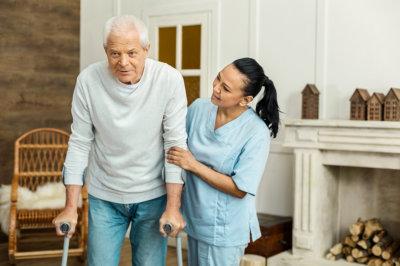 Nurse assisting elderly man to walk